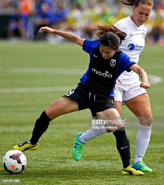 Nahomi Kawasumi of Seattle Reign FC controls the ball against Leigh Ann Robinson of FC Kansas City in the first half of the National Women's Soccer...
