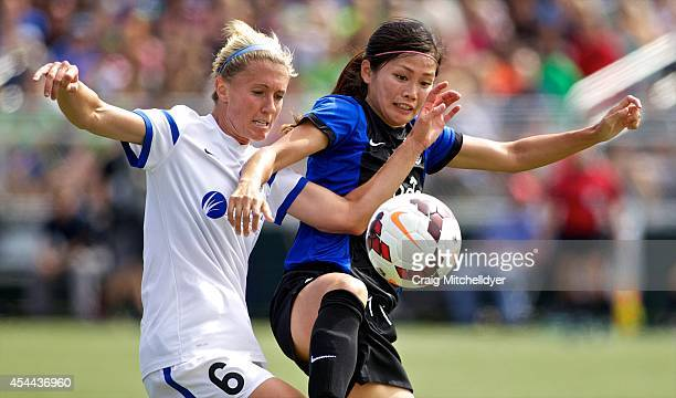 Nahomi Kawasumi of Seattle Reign FC fights for the ball against Jen Buczowski of FC Kansas City in the first half of the National Women's Soccer...