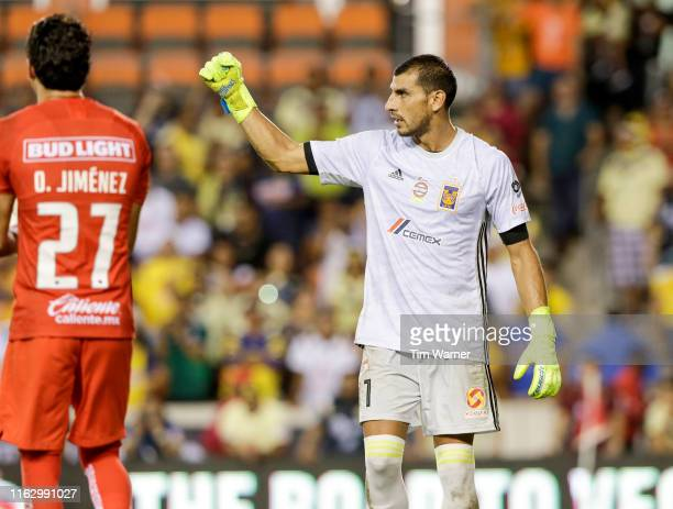 Nahuel Guzman of Tigres UANL celebrates after blocking a shot as Oscar Jimenez of Club America reacts in overtime penalty kicks during the Leagues...