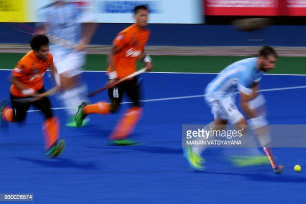 Nahuel Salis of Argentina controls the ball past Malaysia's Fitri Saari and Nabil Noor during their men's field hockey thirdfourth place match of the...