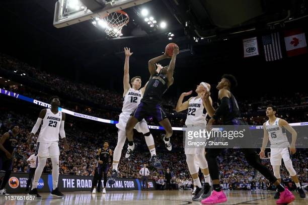 Nahziah Carter of the Washington Huskies shoots against Justin Bean and Brock Miller of the Utah State Aggies during the second half of the game in...