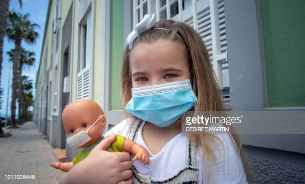 Naidelin and her doll pose wearing a face mask in the street in Santa Cruz on the Canary Island of Tenerife, on April 26, 2020 during a national...