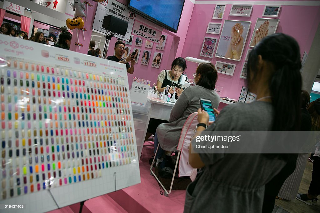 A nail artist (C) works on a visitor's nail during the Tokyo Nail Expo on October 31, 2016 in Tokyo, Japan. According to the organiser, approximately 50,000 people visited this 'largest nail expo in the world' held on October 30th and 31st.