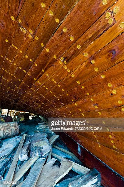 Nail holes filled with putty and freshly oiled timber hull planks on a dhow under construction. Sur, Ash Sharqiyah Region, Gulf of Oman, Sultanate of...
