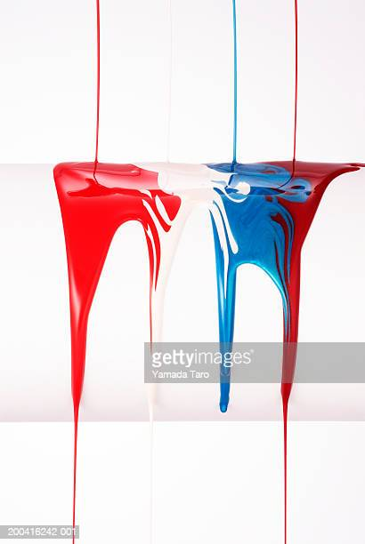 Nail polish being poured over bar, colors blending, close-up