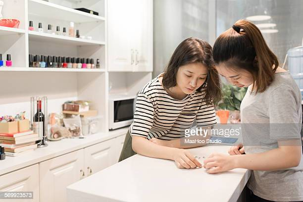 A nail salon owner talking with her staff
