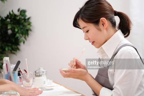 顧客の爪を飾るネイルスタイリスト - マニキュア液 ストックフォトと画像