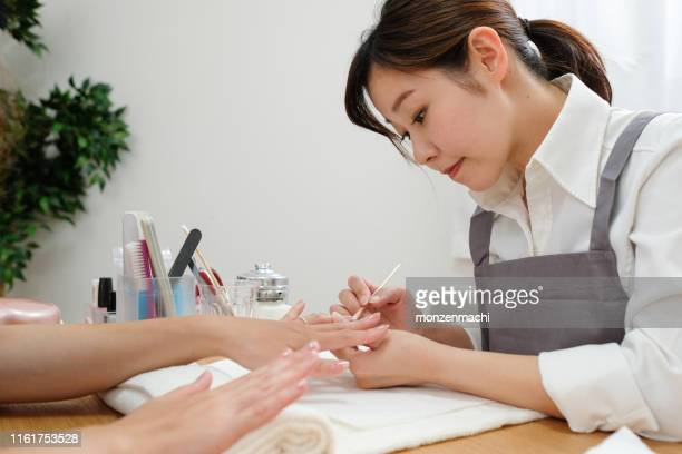 nail stylist decorating fingernail - nail salon stock pictures, royalty-free photos & images