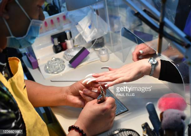 Nail technician works on a customers nails placed through a plastic screen at Top Nails in Birkenhead, north west England on July 13, 2020 as novel...