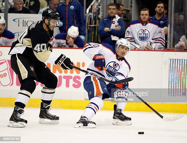 Nail Yakupov of the Edmonton Oilers handles the puck against Maxim Lapierre of the Pittsburgh Penguins during the game at Consol Energy Center on...
