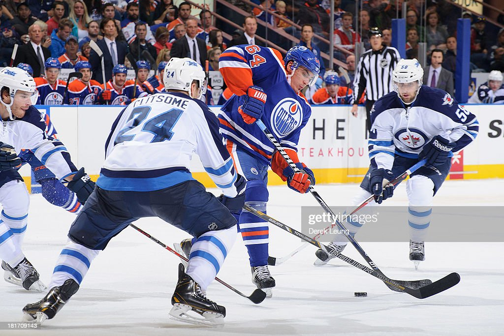 Nail Yakupov #64 of the Edmonton Oilers handles the puck as Eric O'Dell #58 and Grant Clitsome #24 of the Winnipeg Jets look to check him during a preseason NHL game at Rexall Place on September 23, 2013 in Edmonton, Alberta, Canada.