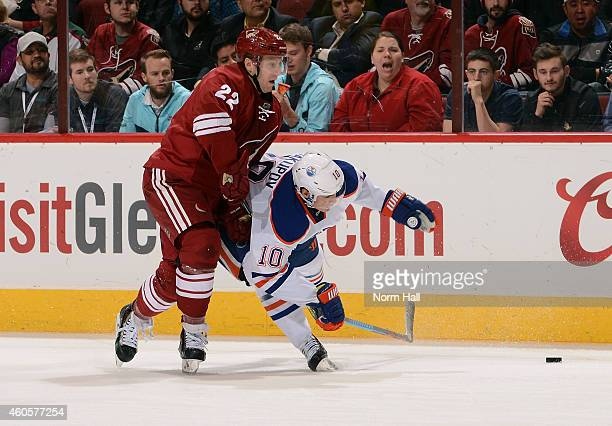 Nail Yakupov of the Edmonton Oilers is knocked to the ice by Brandon McMillan of the Arizona Coyotes during the third period at Gila River Arena on...