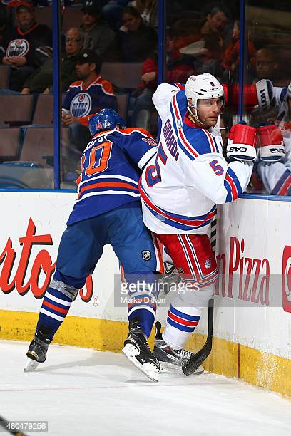 Nail Yakupov of the Edmonton Oilers lands a big hit on Dan Girardi of the New York Rangers on December 14 2014 at Rexall Place in Edmonton Alberta...