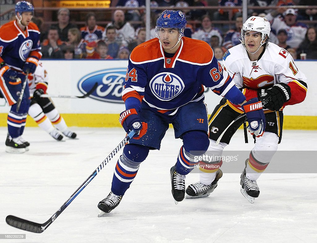 Nail Yakupov #64 of the Edmonton Oilers looks for a pass while Mikael Backlund #11 of the Calgary Flames follows him at Rexall Place on April 1, 2013 in Edmonton, Alberta, Canada.
