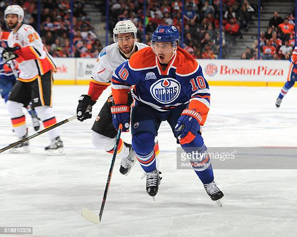 Nail Yakupov of the Edmonton Oilers skates while being pursued by TJ Brodie of the Calgary Flames on April 2 2016 at Rexall Place in Edmonton Alberta...
