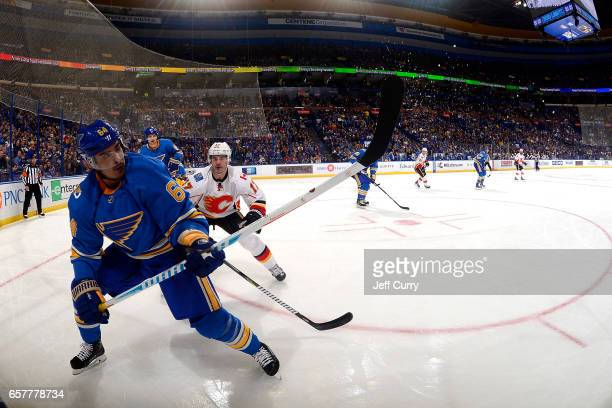 Nail Yakupov of the St Louis Blues clears the puck away from Lance Bouma of the Calgary Flames on March 25 2017 at Scottrade Center in St Louis...