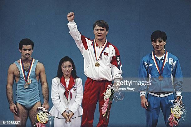 Naim Suleymanoglu of Turkey celebrates his gold medal on the podium alongside silver medallist Stefan Topurov of Bulgaria and bronze medallist Ye...
