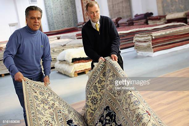 A 'Nain' Persian Rug is folded in the Oriental Rug Centre's main warehouse on March 17 2016 in London England The Oriental Rug Centre in North London...