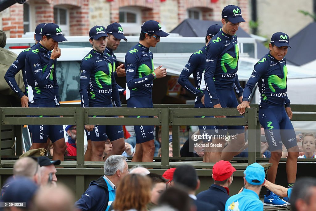 Nairo Quintana (R) leads his Movistar team off a first world war military vehicle as they arrive for the team presentations on June 30, 2016 in Sainte-Mere-Eglise, France.