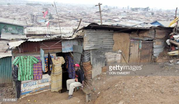 Man watches from a bench as the group following the United Nations Secretary General Ban Ki-moon passes through Kibera slum, Africa's largest slum,...