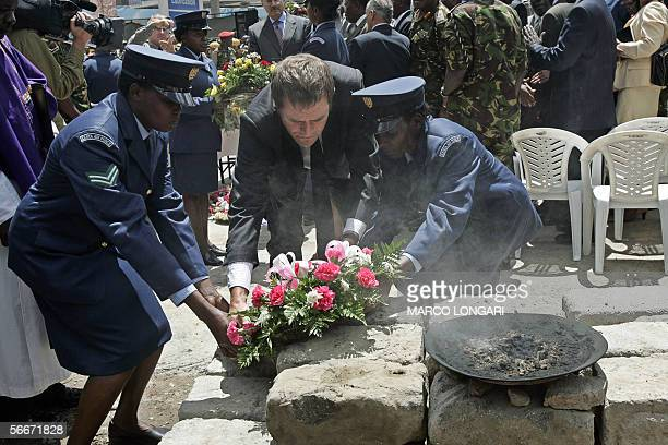 British High Commissioner in Kenya Adam Wood is helped by two Kenyan Air Force female soldiers to lay a wreath 26 January 2006 during a commemoration...