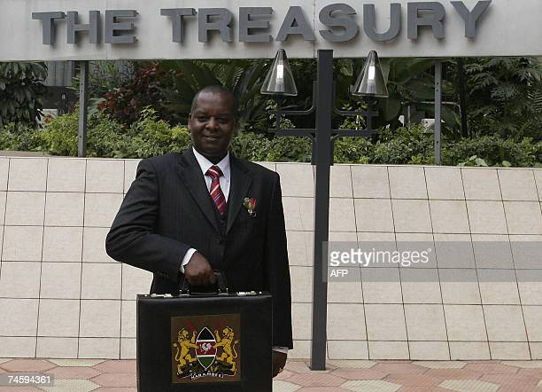 Kenya's Finance Minister Amos Kimunya holds the briefcase before reading of this year budget, where the government scrapped tax on medical equipment...