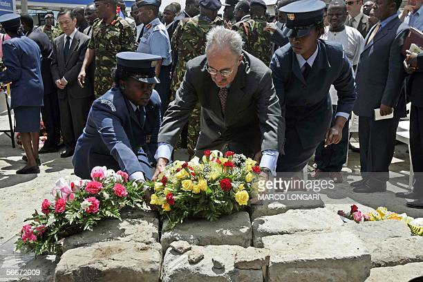 US Ambassador to Kenya William Bellamy is helped by two Kenyan Air Force female soldiers to lay a wreath 26 January 2006 during a commemoration...