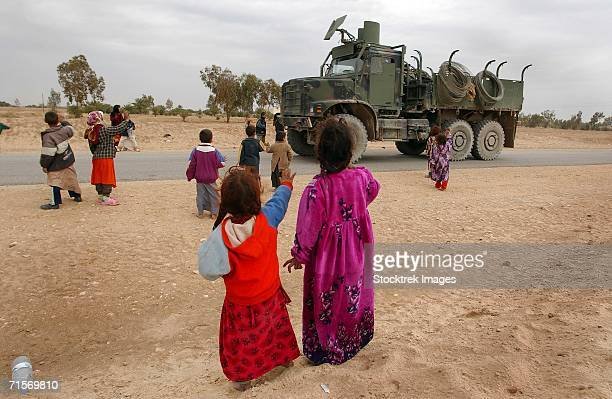 """Najaf, Iraq (January 24, 2005) ? Iraqi children wave to an American convoy that passes on a local road."""