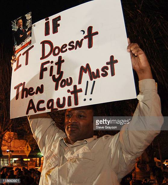 Najee Ali holds a placard with a statement If it doesn't fit you must then you must acquit made famous by the late attorney Johnnie L Cochran at a...