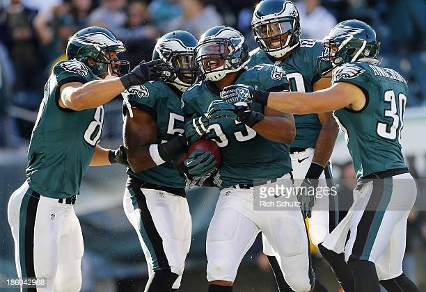 Najee Goode of the Philadelphia Eagles celebrates his touchdown on a fumble recovery with teammates James Casey Emmanuel Acho BJCunningham and safety...