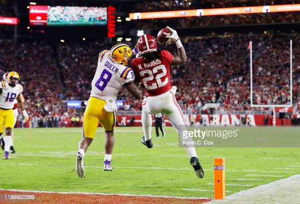 Najee Harris of the Alabama Crimson Tide catches a 15yard touchdown pass as he is defended by Patrick Queen of the LSU Tigers during the third...