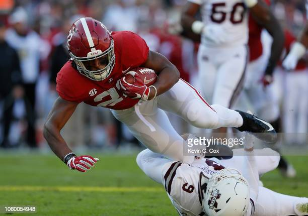Najee Harris of the Alabama Crimson Tide dives over Montez Sweat of the Mississippi State Bulldogs for more yardage at BryantDenny Stadium on...