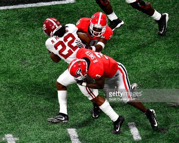 Najee Harris of the Alabama Crimson Tide is tackled by Roquon Smith and J R Reed of the Georgia Bulldogs in the CFP National Championship presented...