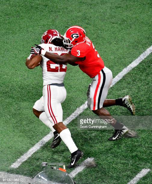 Najee Harris of the Alabama Crimson Tide is tackled by Roquon Smith of the Georgia Bulldogs in the CFP National Championship presented by ATT at...