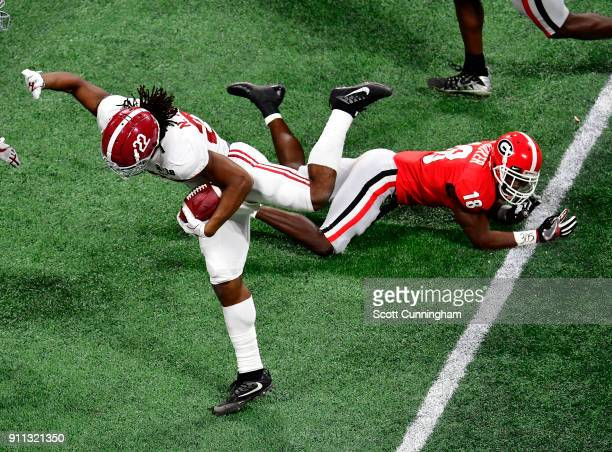 Najee Harris of the Alabama Crimson Tide is upended by Deandre Baker of the Georgia Bulldogs in the CFP National Championship presented by ATT at...
