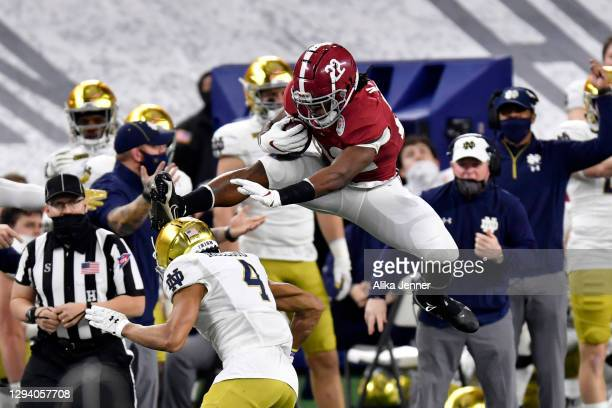 Najee Harris of the Alabama Crimson Tide leaps over Nick McCloud of the Notre Dame Fighting Irish during the first half of the College Football...