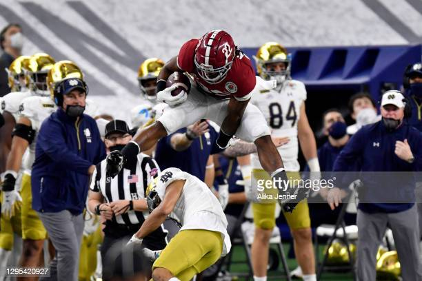 Najee Harris of the Alabama Crimson Tide leaps over Nick McCloud of the Notre Dame Fighting Irish during the College Football Playoff Semifinal at...