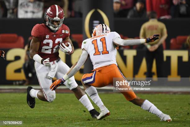 Najee Harris of the Alabama Crimson Tide runs against Isaiah Simmons of the Clemson Tigers in the CFP National Championship presented by ATT at...