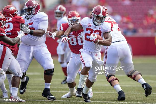 Najee Harris of the Alabama Crimson Tide runs the ball in the second half during a game against the Arkansas Razorbacks at Razorback Stadium on...