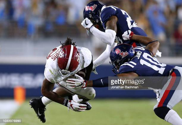 Najee Harris of the Alabama Crimson Tide runs with the ball as Jacquez Jones of the Mississippi Rebels defends during the second half of a game at...