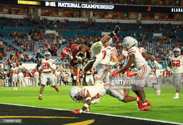 Najee Harris of the Alabama Crimson Tide rushes for a 26 yard touchdown during the second quarter ahead of Josh Proctor of the Ohio State Buckeyes of...