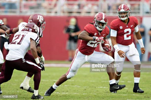 Najee Harris runs the ball after taking a hand off from Jalen Hurts of the Alabama Crimson Tide during a game against the Texas AM Aggies at...