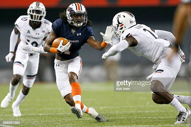 Najee Ray of the Tennessee-Martin Skyhawks stiff-arms Tyrell Gilbert of the Cincinnati Bearcats while carrying the ball during the third quarter at...