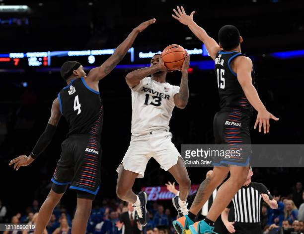 Naji Marshall of the Xavier Musketeers shoots the ball as Paul Reed and Oscar Lopez Jr. #15 of the DePaul Blue Demons defend in the second half...
