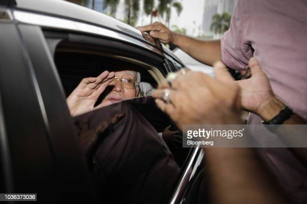 Najib Razak Malaysia's former prime minister is surrounded by police officers and supporters as he leaves the Kuala Lumpur Courts Complex in Kuala...