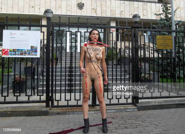 Naked activist of Femen stands outside the Embassy of Poland during the protest. An activist of the women's movement FEMEN took part in her...