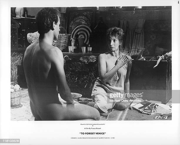 Naked actor sitting with semi clad actress in a scene from the film 'To Forget Venice' 1980