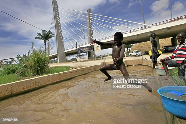 A naked Angolan boy jumps into a small canal from the Catumbla River under the newly constructed bridge in Lobito town about 25 km out of Benguela...