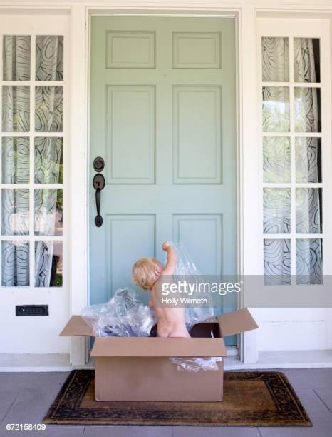 Naked baby boy in cardboard box in doorway