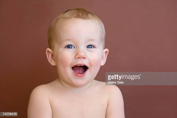 'Naked baby boy (21-24 months) laughing in studio, head and shoulders'